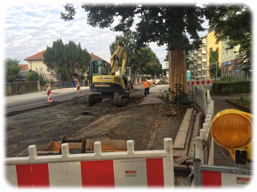 Arbeiter reißen mit einem Bagger die provisorische Fahrbahn auf der Hepkestraße ab. Danach bringen sie die finale Fahrbahndecke auf. Zuvor hatten sie eine neue Brücke errichtet, über die die Hepkestraße den Blasewitz-Grunaer-Landgraben quert. Foto: Heiko Weckbrodt