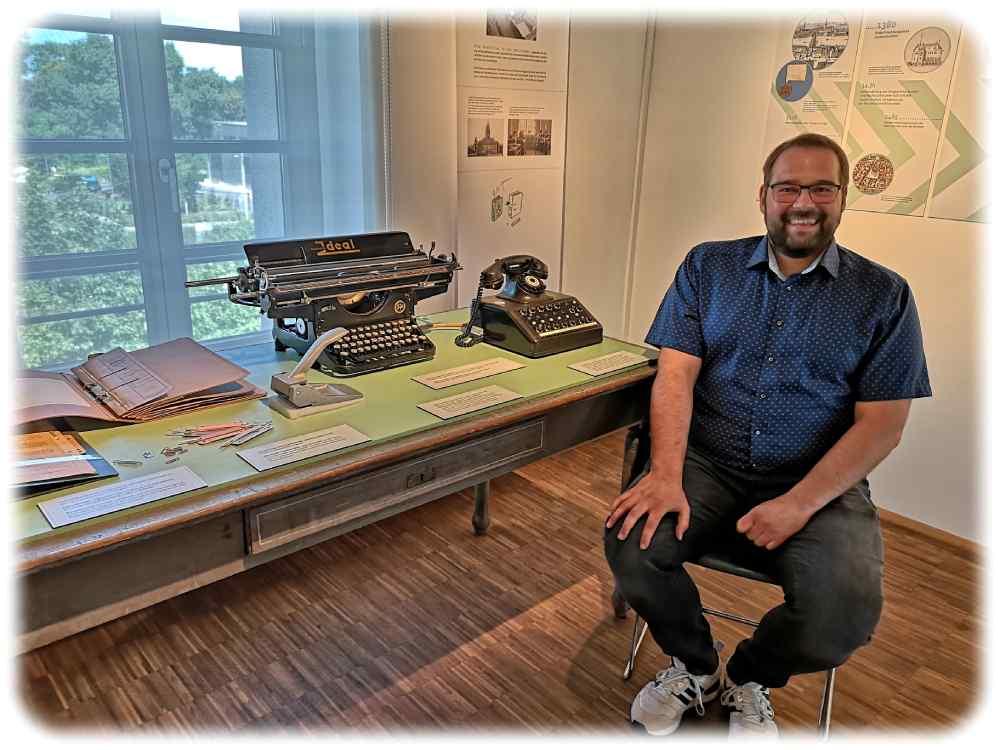 Dr. Marco Iwanzeck an einem für die Ausstellung aufgebautem Behörden-Schreibtisch der vordigitalen Zeit. Der Sat1-Aufkleber auf dem Fernsprecher lässt vermuten, dass dieser Telefonvorläufer sogar noch nach der Wende im Einsatz war. Foto: Heiko Weckbrodt